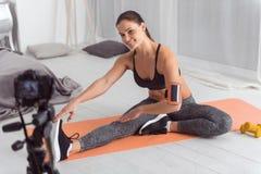 Lächelnde muskulöse Sportlerin, die Übungen für ihr Blog tut Stockbilder