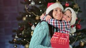 Lächelnde Mutter der glücklichen Familie und nette kleine Sonne, die umarmende und glaubende Neigung Santa Claus-Hutes tragen stock video
