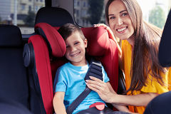 Lächelnde Mutter, die den Sicherheitsgurt des Sohns sitzend im Kindersitz überprüft Lizenzfreies Stockbild