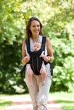 Lächelnde Mutter, die draußen mit Baby im Riemen geht lizenzfreie stockbilder