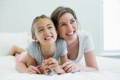 Lächelnde Mutter, die ihre Tochter beim Lügen auf Bett im Schlafzimmer umfasst Lizenzfreie Stockfotos
