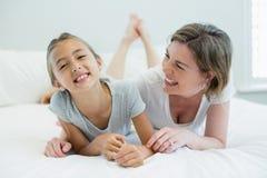 Lächelnde Mutter, die ihre Tochter beim Lügen auf Bett im Schlafzimmer umfasst Lizenzfreies Stockfoto