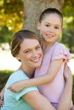 Lächelnde Mutter, die ihre Tochter am Park umfasst Stockfotos