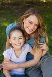 Lächelnde Mutter, die ihre Tochter am Park umfasst Lizenzfreie Stockbilder