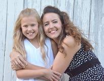 Lächelnde Mutter, die junge blonde Tochter umarmt Stockbilder