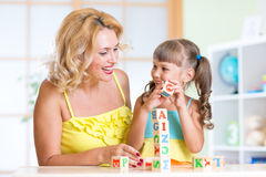 Lächelnde Mutter, die Mädchen unterstützt, wenn Block gespielt wird Lizenzfreie Stockfotografie