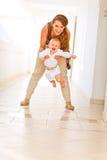 Lächelnde Mutter, die mit ihrem entzückenden Schätzchen spielt Lizenzfreies Stockfoto