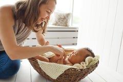 Lächelnde Mutter, die mit neugeborenem Baby, Profil spielt lizenzfreies stockbild