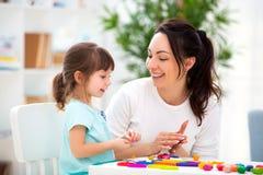 Lächelnde Mutter hilft einer kleinen Tochter sculpt Figürchen vom Plasticine Kind-` s Kreativität Glückliche Familie lizenzfreies stockfoto