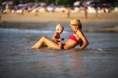 Lächelnde Mutter mit einer Kinderschwimmen im Meer Stockfotos