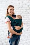 Lächelnde Mutter mit neugeborenem Baby im Babyriemen stockfoto