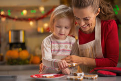 Lächelnde Mutter und Baby, die Weihnachtsplätzchen machen stockfotografie