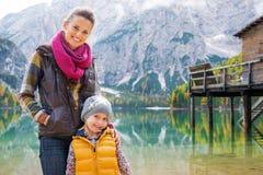 Lächelnde Mutter und blonde Tochter, die am See Bries aufwerfen Lizenzfreies Stockfoto