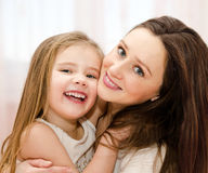 Lächelnde Mutter und ihr kleines Mädchen, die zusammen spielen Stockbilder