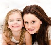 Lächelnde Mutter und ihr kleines Mädchen, die zusammen spielen Stockfotografie