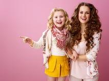Lächelnde Mutter und Kind lokalisiert auf dem rosa Zeigen auf etwas stockfotografie