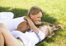Lächelnde Mutter und kleine Tochter auf Natur. Glückliche Menschen draußen stockfotografie