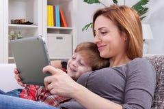 Lächelnde Mutter und Sohn, der Tablette verwendet Stockbilder
