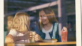 Lächelnde Mutter und Tochter, die frühstücken Stockfotos