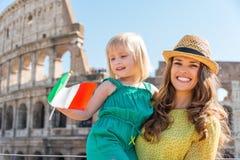 Lächelnde Mutter und Tochter, die italienische Flagge durch Colosseum wellenartig bewegen Stockbild