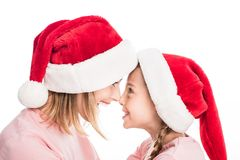 Lächelnde Mutter und Tochter, die Sankt-Hüte berühren Nasen trägt, stockfoto