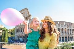 Lächelnde Mutter und Tochter mit rosa Ballon durch Colosseum Stockfoto