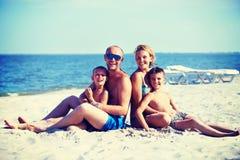 Lächelnde Mutter und Vater mit Kindern auf dem Strand Stockbild