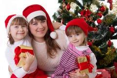 Lächelnde Mutter und zwei Töchter unter Weihnachtsbaum Lizenzfreies Stockbild
