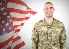 Lächelnde nahe flatternde amerikanische Flagge des Soldaten Lizenzfreie Stockfotografie