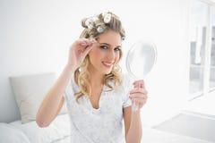 Lächelnde natürliche Blondine, die Pinzette auf ihrer Augenbraue verwendet lizenzfreies stockbild