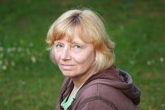 Lächelnde natürliche reife Frau Stockfotografie