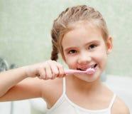 Lächelnde nette bürstende Zähne des kleinen Mädchens lizenzfreie stockfotografie