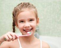 Lächelnde nette bürstende Zähne des kleinen Mädchens im Badezimmer stockfoto