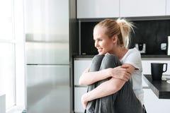 Lächelnde nette Dame, die beiseite beim Sitzen in der Küche schaut Stockfoto