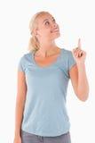 Lächelnde nette Frau, die auf copyspace zeigt Stockfoto