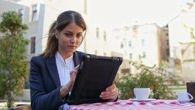 Lächelnde nette junge Frau, die Tablette in der Terrasse des Cafés und des Getränkkaffees verwendet stock video footage