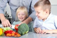 Lächelnde nette Tochter und Sohn, die ein Abendessen kochen Kleine Kinder, die einen bunten Pfeffer mit Vater hacken stockbilder