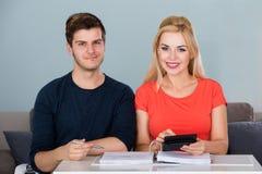Lächelnde Paar-Rechenrechnung unter Verwendung des Taschenrechners Stockfotografie