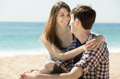 Lächelnde Paare auf sandigem Strand Stockbilder