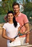 Lächelnde Paare auf Tennisgericht Stockfotos