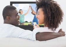 Lächelnde Paare beim Aufpassen des Golfs im Fernsehen Stockbild