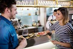 Lächelnde Paare beim Essen des Weins durch Zähler Stockbilder