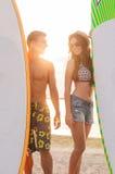 Lächelnde Paare in der Sonnenbrille mit Brandungen auf Strand Lizenzfreies Stockbild
