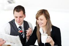 Lächelnde Paare der Wirtschaftler, die Zeitung lesen Lizenzfreie Stockfotos