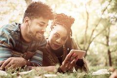 Lächelnde Paare des Afroamerikaners im Park unter Verwendung des Handys Stockfoto
