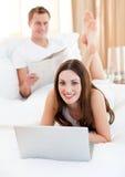 Lächelnde Paare, die Aktivitäten haben, auf Bett zu liegen Stockbild