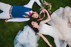 Lächelnde Paare, die auf das Gras legen Lizenzfreie Stockfotos