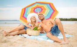Lächelnde Paare, die auf dem Strand ein Sonnenbad nehmen Stockfotos