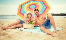 Lächelnde Paare, die auf dem Strand ein Sonnenbad nehmen Lizenzfreies Stockbild