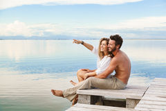 Lächelnde Paare, die auf den Horizont gehen und zeigen lizenzfreies stockfoto